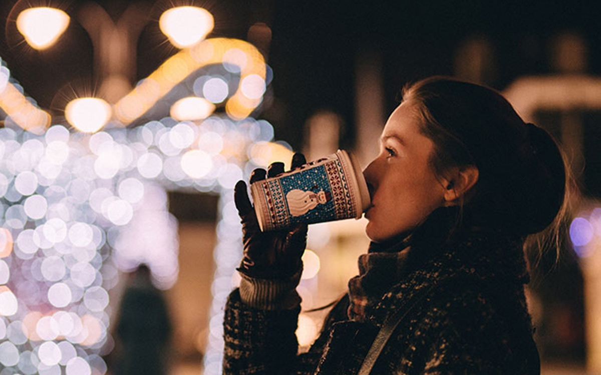 holiday-activities-woman-drinking-coffee-christmas-lights-aliat